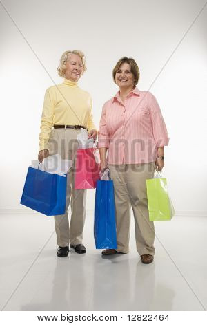 Caucasian senior woman and middle aged woman holding gift bags smiling at viewer.