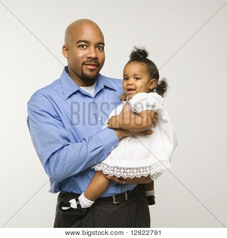 African American man holding infant girl standing against white background.