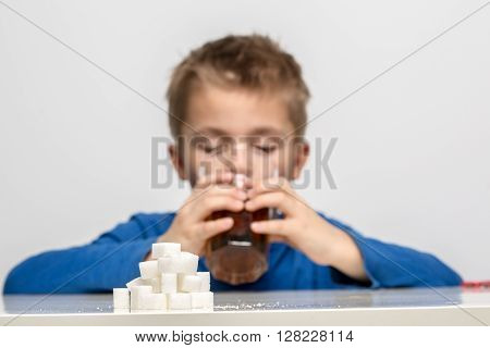 Glass full of soft drink next to it is the amount of sugar used in it. Shallow DOF, sugar cubes are sharp.