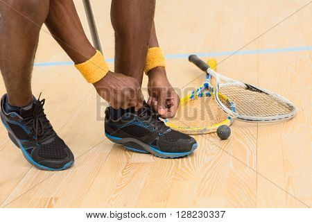 Squash player man preparing for game on court. Black man adjusting his training shoes indoors. Sports concept.