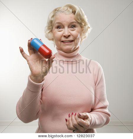 Caucasian senior woman holding oversized pill at viewer.