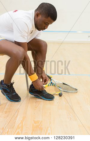 Squash player man preparing for great battle in squash on court. Young black man sitting court and adjusting his training shoes.