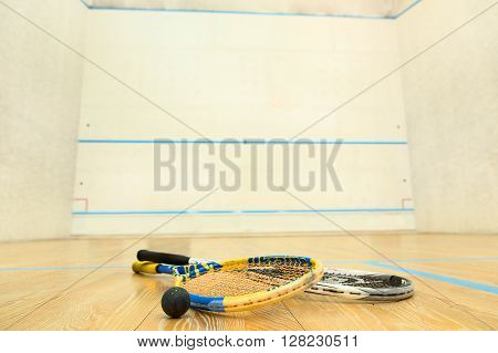 Squash racket closeup are represented in empty court. Special equipment is ready for use. Squash concept.