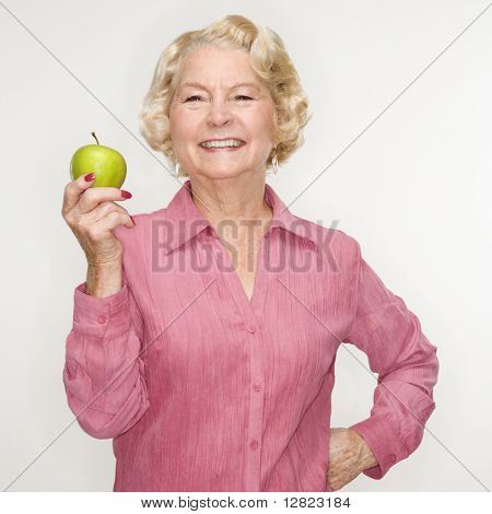 Caucasian senior woman holding apple smiling at viewer.