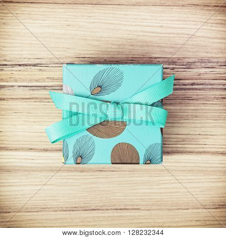 Painted gift box with ribbon on the wooden background. Holiday symbol. Symbolic object. Birthday theme.