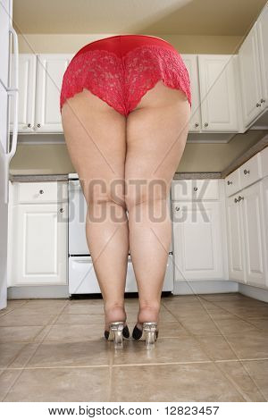 Back view of full figured Caucasian young woman in sexy red lingerie bending over in kitchen.