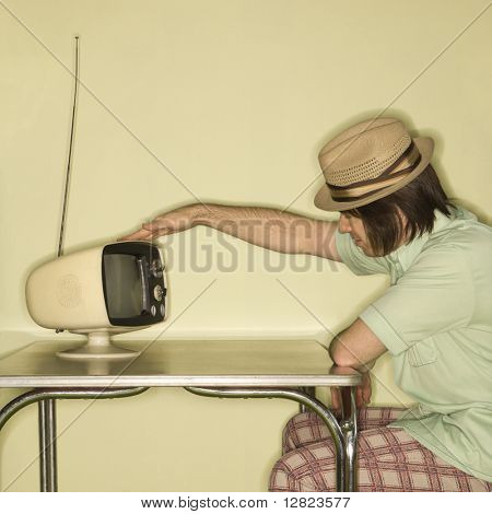 Side view of Caucasian mid-adult man wearing hat sitting at 50's retro dinette set tapping old television set.
