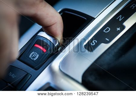 Close-up shot with the detail of a parking brake in a car.