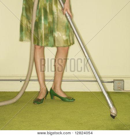 Close-up of Caucasian female legs with vacuum extension against green retro carpet.
