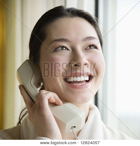 Taiwanese mid adult woman in bathrobe talking on phone and smiling.