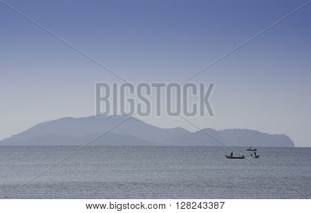 Silhouetted Fishing Boat Showing Misty Mountains Early Morning Sun.