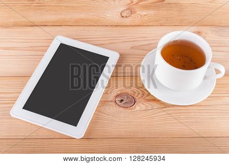 Tablet computer and a cup of tea on a wooden table.