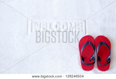 Welcome mat with red child sandals on floor