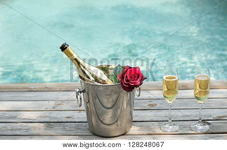 Champagne bottle in ice bucket with flower and champagne glass by swimming pool