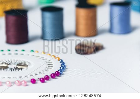 Sewing background. Accessories for needlework on white cloth background. scissors, buttons, measuring tape, sewing supplies. Set for needlework top view.