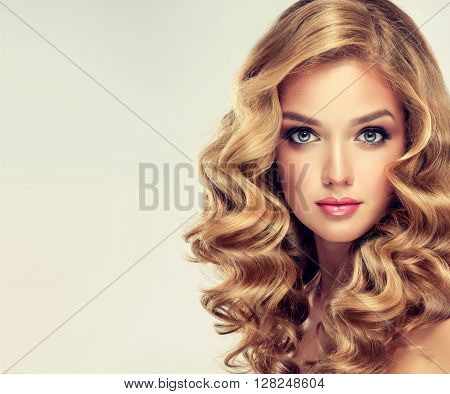 Beautiful girl with long wavy hair . Blonde  with curly hairstyle .