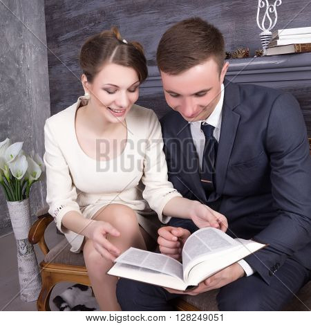the young beautiful woman and the man in the relations a young family thumbs through the book