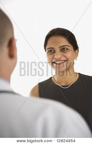 Caucasian mid adult male physician talking with Indian woman patient.