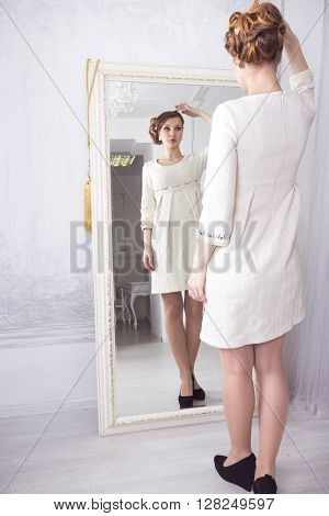 the young beautiful woman in a white dress admires in a mirror
