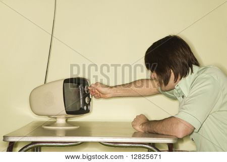 Side view of Caucasian mid-adult man sitting at 50's retro dinette set turning old television knob.