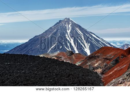 Beautiful Kamchatka volcanic landscape: view to top of cone of Koryaksky Volcano from scenery active crater of Avacha Volcano on a sunny day and blue sky. Russian Far East Kamchatka Peninsula Avachinsky-Koryaksky Group of Volcanoes.
