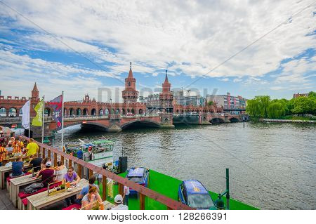BERLIN, GERMANY - JUNE 06, 2015: Spree river cross under oberbaumbrucke, square on a side with excelent view. People eating and talking