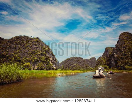 Vintage retro effect filtered hipster style image of tourists on boats in Tam Coc-Bich Dong Ngo Dong river in popular tourist destination near Ninh Binh, Vietnam