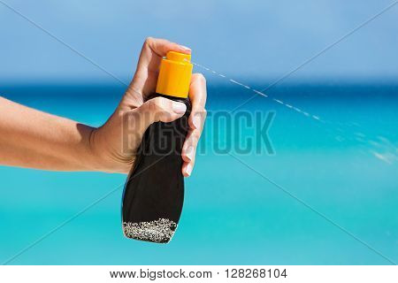 Female Hand Applying Sunscreen Protection Cream Against Turquoise Caribbean Sea Water And Blue Sky