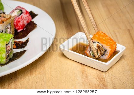 Sushi roll made dish. Sushi assorti on white plate with chopsticks nut souce glass of wine. Evening date closeup food photography
