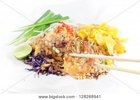 Fried noodle Thai style with prawns. Stir fry noodles with shrimp in (Pad Thai) Thai Cuisine on white color wrapper food. selective focus to chopsticks tong shrimp