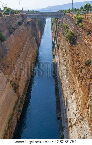 High steep banks of the Corinth canal is gradually overgrown with bushes and even trees. Ancient Corinth. Greece.