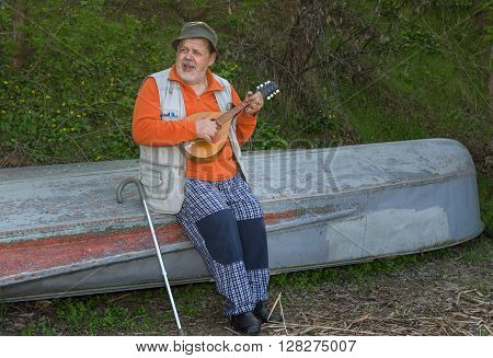 Senior man sitting on an old reversed boat and singing playing himself with mandolin