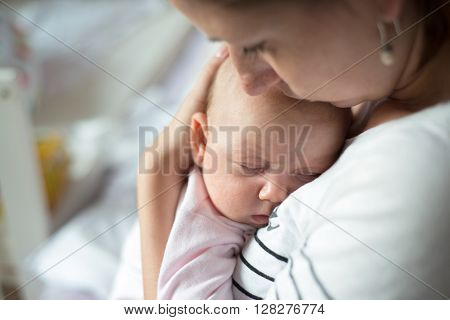 Close up of young mother holding her cute baby daughter sleeping in her arms