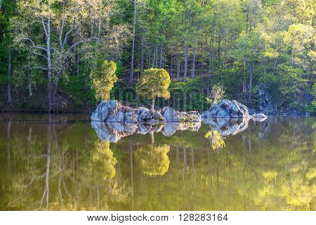 Trees and Rocks Reflected on Calm Water.  A small island and trees in the reflected in the calm surface of the Widewater area of the C&O Canal National Historic Park, Potomac, Maryland.
