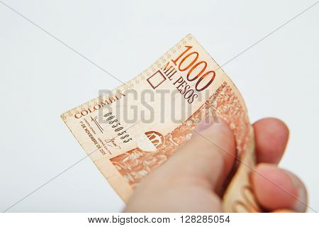 Male hand holding National currency of Colombia