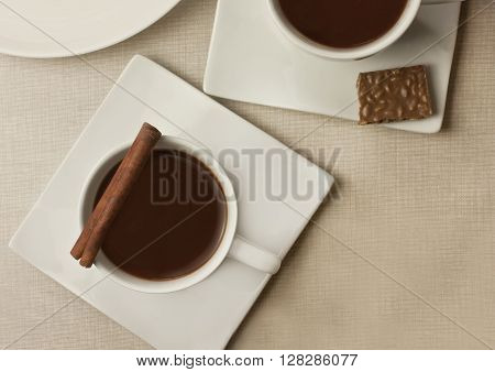 Two cups of dark hot chocolate with a cinnamon stick on a burlap background texture with a piece of chocolate and a place for text