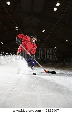 Caucasian woman hockey player sliding kicking up ice.