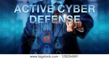 Computer security agent is touching ACTIVE CYBER DEFENSE on an interactive virtual display. Information technology concept and security metaphor for strike-back doctrine and pre-emptive operations.