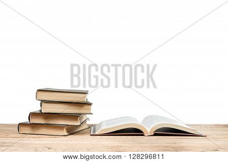 Open book near the pile of book lying on a wooden table isolated on white background