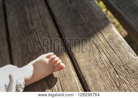 Bare foot of a male baby over weathered wooden background. Natural light