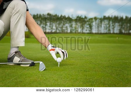 male hand in glove placing golf ball on tee over beautiful golf course with blue sky