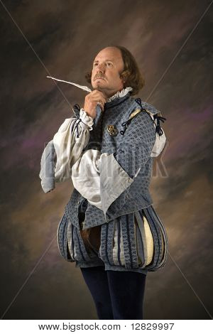 William Shakespeare in period clothing holding feather pen with thoughtful expression.