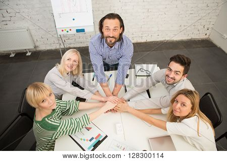 Coworking of businessteam. Happy people joining hands all together and showing team work in their company, firm or enterprise.