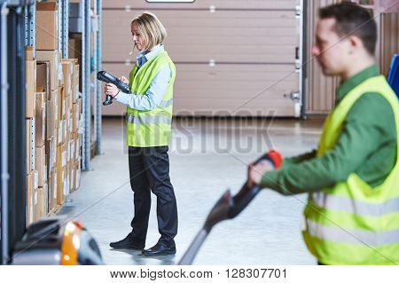 Warehouse Management System. Workers with barcode scanner and stacker