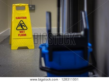 Mop bucket and caution wet floor sign in the building