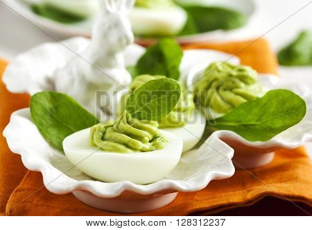 Deviled eggs with avocado and spinach served on plate