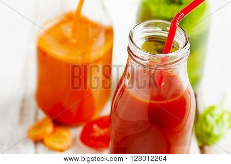 Fruits and vegetable juice in bottle: Apple and spinach juice carrot juice and tomto juice.