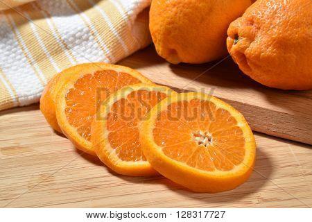 Fresh ripe sliced organic oranges on a cutting board