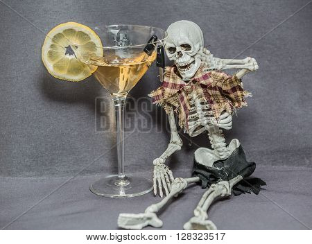 A skeleton sitting near the glass with alcohol fluid and looking at car keys hanging on edge of the glass