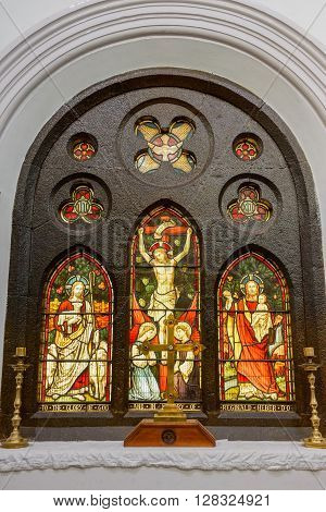 Trichy India - October 15 2013: Crucifixion of Jesus painted on glass and displayed behind altar of Saint John's Church. Extra are Jesus with lambs and Jesus with toddler. Warm reds and yellows.
